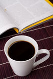 Coffee time. Still life with mug full of coffee and magazine Royalty Free Stock Photography