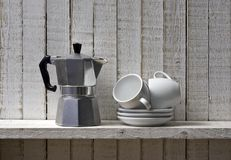 Coffee time. Coffee pot and pile of coffee cups on shelf Royalty Free Stock Photos