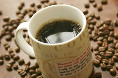 Coffee time. Freshly poured cup of coffee against a backdrop of coffee beans royalty free stock image