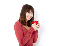 Coffee time. Beautiful young woman holding a cup of coffee, against a white wall Stock Photos
