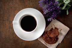 Coffee time. Hot coffee and cookie with flower on wood table Stock Images