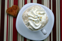 Coffee time. Cup of coffee with whipped cream, chocolate and heart cookie royalty free stock image