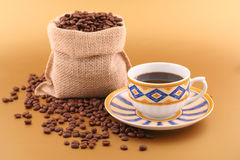 Coffee time. Cup of coffee, coffee canvas bag and lots grains of coffee on gold background Stock Photo