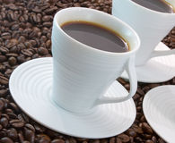 Coffee Time. Fresh coffee in white espresso cups with coffee beans Stock Photo