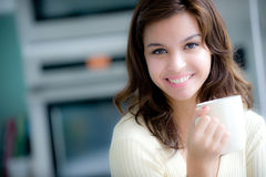 Coffee Time. A young woman having coffee in the kitchen royalty free stock image