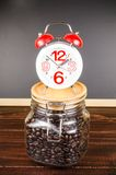 Coffee time,alarm clock with coffee bean in glass bottle Royalty Free Stock Image