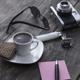 Coffee time. Analogue photo camera on a table with coffee and paper notes Stock Images