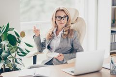 It is coffee time! Attractive charming carefree female boss clot. Hed in grey jacket and white shirt is drinking tea and watching videos on the internet Stock Images