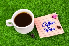 Coffee time with coffee. Coffee time word in memo with coffee cup , coffee bean and dried rose bud on grass royalty free stock images