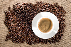 Coffee time concept. Cup of coffee with coffee beans on burlap background Stock Image