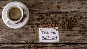 Coffee time concept. Cup of coffee on saucer and coffee beans over old rough wooden surface and white sheet of paper with Time For Action sign. Copy space Royalty Free Stock Photos