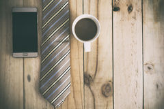 Coffee time concept. Smartphone and necktie on wood table. Vintage style Royalty Free Stock Photos