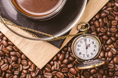 Coffee time concept with vintage pocket watch on coffee beans Royalty Free Stock Images