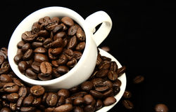 Coffee time, a cup of beans. On a black background Stock Images