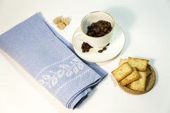 Coffee time. A cup with coffee beans, biscuits, lambs of sugar, blue napkin on a white background stock photos