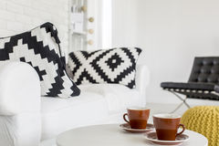 Coffee time in a modern living room. Cropped picture of a coffee table and a sofa in a modern living room stock images