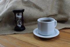 Coffee time, coffee mug and an hourglass on the table. Cofe Stock Image