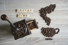 Coffee time quote word with Roasted coffee beans placed in the s. Hape of a cup and saucer on wooden background, with vintage wooden grinder royalty free stock image