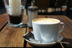 Coffee-time in summer. Close-up picture of a white porcelain cup of coffee on a wooden table Stock Photo