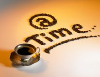 At coffee time. Symbolic picture showing a coffee cup and written text made of coffee beans, illuminated with orange light Royalty Free Stock Photo