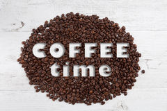Coffee time text on scattered coffee beans and white rustic wood Royalty Free Stock Photo