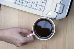 Coffee time at work. A cup of coffee and computer Royalty Free Stock Images
