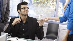 Coffee to the boss. Male boss getting cup of coffee from secretary, smiling Stock Photos