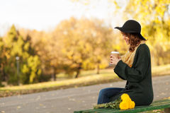 Coffee to go. Close up of young woman holding a cup of takeaway coffee cup, shallow depth of field Stock Photo