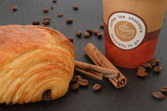 Coffee to go and croissant with coffee beans. Coffee to go and croissant with coffee beans on a black background Stock Photography