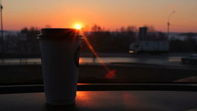 Coffee to go cup standing on car panel sunset and city road traffic background stock video footage