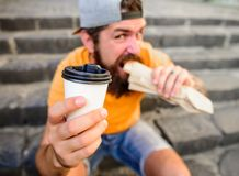 Coffee to go and street food choice of youth. Man hipster have quick lunch sit stairs background. Paper cup coffee and. Hot dog street food traditional snack stock photo