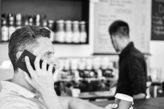 Coffee to go useful option for busy people. Call friend to have drink together. Guy busy speak phone while relax coffee. Break. Ready to hear you. Man holds cup royalty free stock image