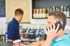 Coffee to go useful option for busy people. Call friend to have drink together. Guy busy speak phone while relax coffee. Break. Ready to hear you. Man holds cup royalty free stock photography