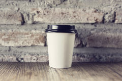 Coffee to go on a wooden table with vintage style wall Royalty Free Stock Photo