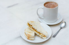 Coffee and toasted bread. Hot coffee in a classic porcelain cup and toasted bread filled with margerine and coconut gem served on table stock photography