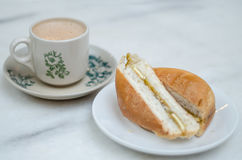 Coffee and toasted bun. Hot coffee in a classic porcelain cup and toasted bun filled with margerine and coconut gem served on table stock photography