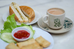Coffee and toasted bun. Hot coffee in a classic porcelain cup and toasted bun filled with margerine and coconut gem served on table along with other beverages stock images