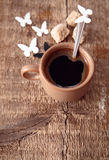 Coffee. Toned image, cup of black coffee, brown sugar, spoon, paper butterflies, wooden background royalty free stock image