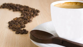 Coffee trail. Close up of a cup of coffee, chocolate spoon and coffee beans. Focus on the coffee Royalty Free Stock Photography