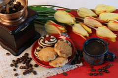 Coffee, tulips, coffee grinder and cookies, coarsely. A cup of coffee and cookies on a saucer, yellow tulips and coffee beans, a coffee grinder Royalty Free Stock Images