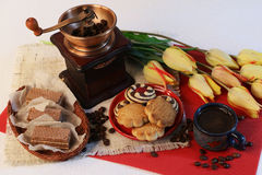 Coffee, tulips, coffee grinder and cookies. A cup of coffee and cookies on a saucer, yellow tulips and coffee beans, a coffee grinder Stock Photo
