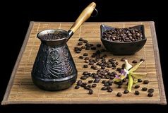 Coffee turk with coffee beans and orchid. On black background isolated Royalty Free Stock Photography