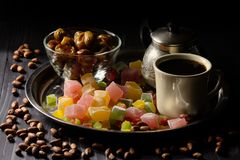 Coffee with Turkish Delight, candied fruits, pinuts and dates on darck background. A cup of coffee with sweats peanuts and dates on dark background of black Royalty Free Stock Images