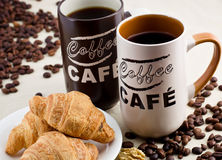 Coffee. Two cups of coffee with croissants and elements walnuts Royalty Free Stock Images