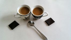 Coffee in two small cups with spoon and chocolate on the side. Two cups of coffee, and two pieces of dark chocolate on the side with spoon on white table Royalty Free Stock Photos