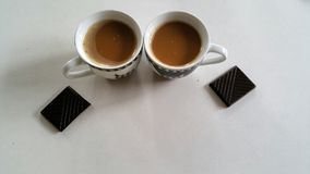Two coffees in small cups with chocolate on the side Royalty Free Stock Photography