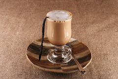 Coffee Vanilla Latte with bean in tall glass. On hessian background, shallow DOF Royalty Free Stock Photography