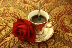 Coffee victorian cup red rose. Victorian coffee cup and one red rose Stock Images