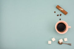 Coffee and in vintage cup with cinnamon and shugar on turquoise background. Top view, copy space. Royalty Free Stock Images