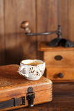 Coffee in vintage cup with Nostalgic coffee grinder on backgroun Stock Photos